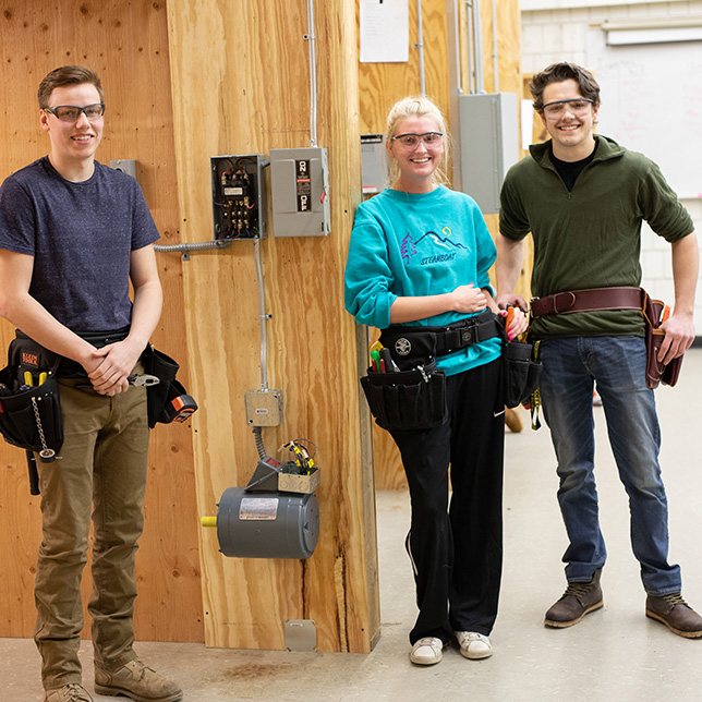 Three Construction students standing by a circut breaker.