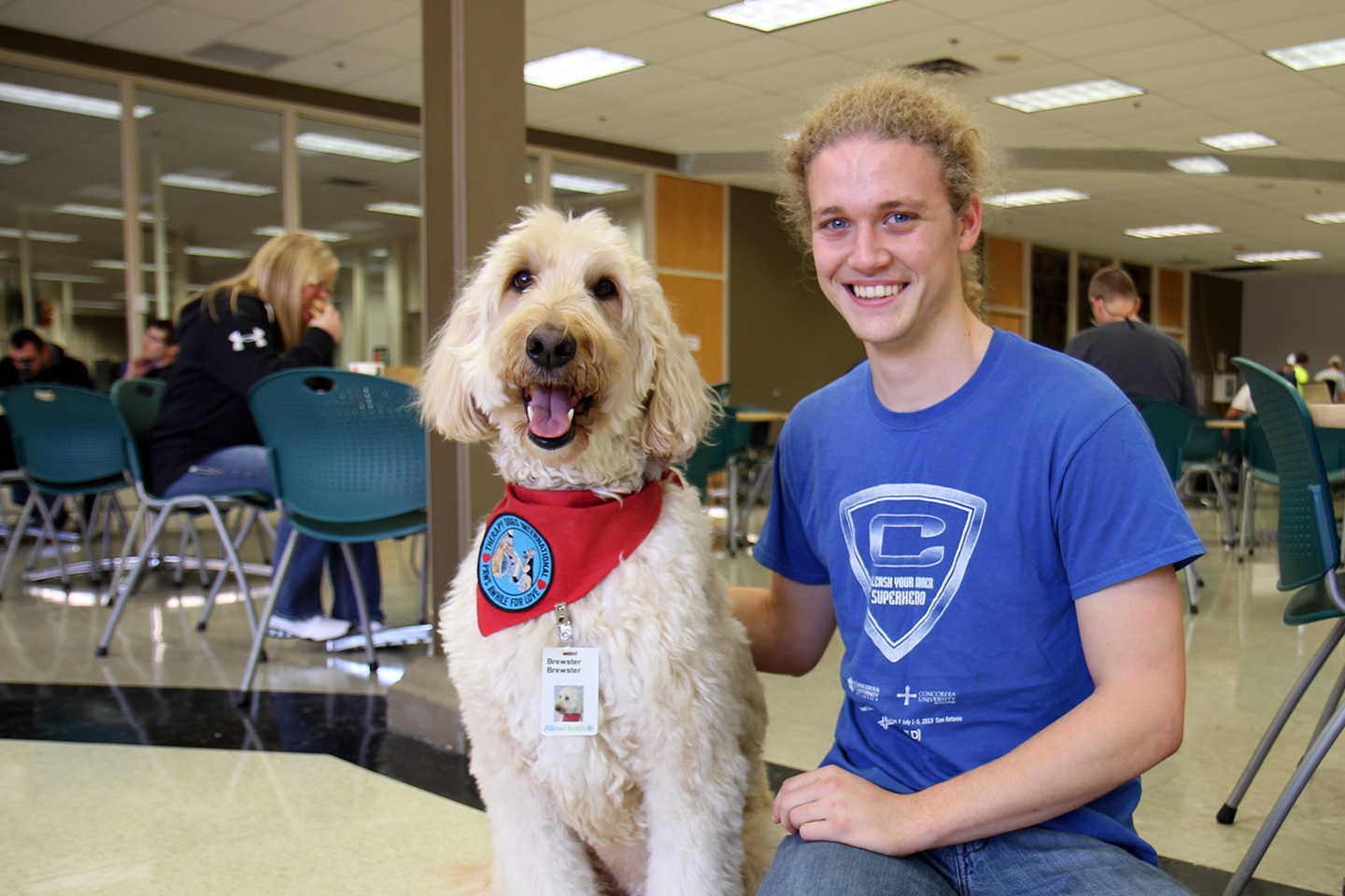 "At Anoka Technical College monthly ""Paws for Stress Relief"" event, student Daniel Stinogel poses with therapy dog Brewster."